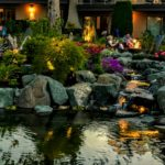 Outdoor pond and gardens with people sitting on patio